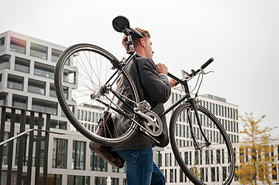 Young businessman carrying bicycle, Munich, Bavaria, Germany - p1026m992116f by Slavica