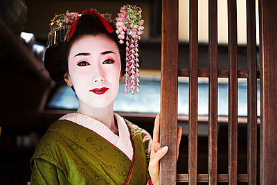 A woman dressed in the traditional geisha style, wearing a kimono and obi, with an elaborate hairstyle and floral hair clips, with white face makeup with bright red lips and dark eyes.  - p1100m1185737 by Mint Images
