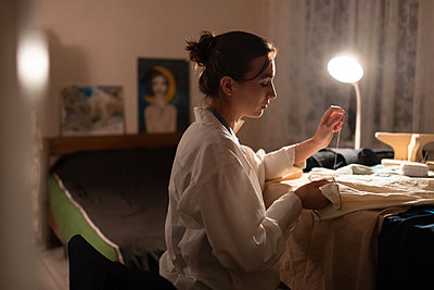 Seamstress sewing at home in lamplight - p1166m2218577 by Cavan Images