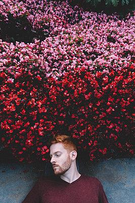 Rothaariger Mann liegt mit dem Kopf im Blumenbeet - p1491m1582706 von Jessica Prautzsch