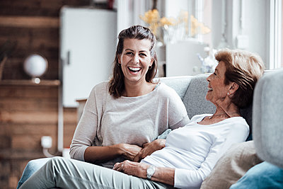 Laughing woman sitting by grandmother on sofa at home - p300m2274905 by Gustafsson