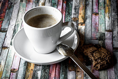 Cup of coffee and chocolate cookies on coloured wood - p300m950648f by Sandra Roesch