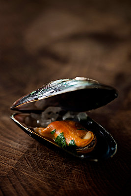 Open mussel on wooden table - p426m1085324f by Fredrik Telleus