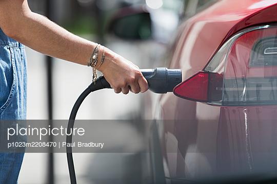 Woman recharging electric car - p1023m2208470 by Paul Bradbury