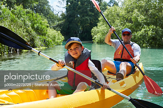 Smiling boy looking away while canoeing with father in lake - p300m2273725 by Stefanie Aumiller
