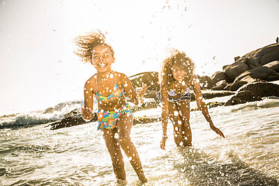 Happy mother and daughter splashing with water in the sea - p300m2167105 by Floco Images