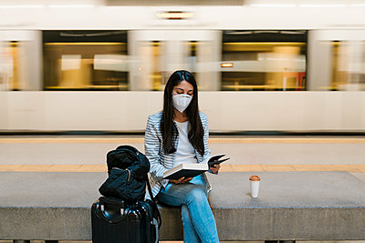 Woman reading book while sitting against moving train at metro station - p300m2240697 by Ezequiel Giménez