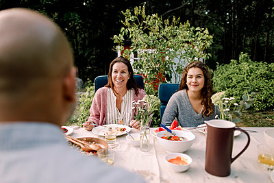 Smiling woman and daughter looking at father while sitting by dining table in yard - p426m2227824 by Maskot