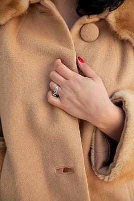Woman closing her coat - p4950279 by Jeanene Scott