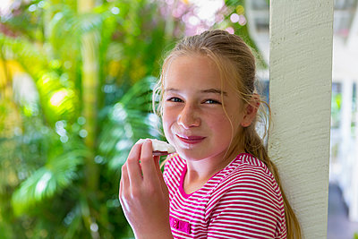 Smiling Caucasian girl eating piece of coconut - p555m1490990 by Marc Romanelli