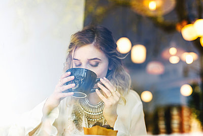 View through coffee shop window of woman drinking coffee - p924m1174890 by Lena Mirisola