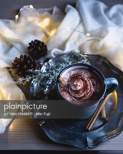 High angle view of coffee with cream and cinnamon powder on table - p1166m1094897f by Miki Fujii