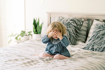 Little toddler girl playing peek-a-boo on her parent's bed. - p1166m2152347 by Cavan Images
