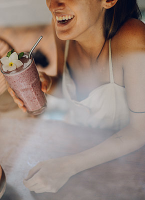 a girl feel so happy drinking a delicious strawberry smoothies - p1166m2261237 by Cavan Images