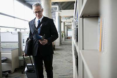 Mature businessman with passport and airline ticket walking with suitcase in office - p1192m1517121 by Hero Images