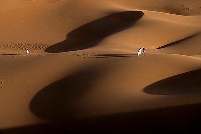 People exploring Erg Chebbi dunes in Sahara Desert - p343m1475892 by David Santiago Garcia