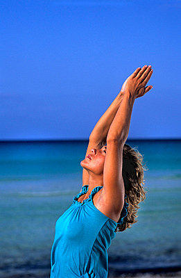 Woman doing yoga at the beach - p8850295 by Oliver Brenneisen