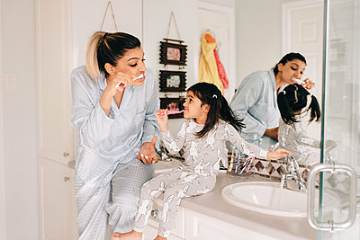 Girl and mother brushing their teeth in bathroom - p924m2091240 by Sara Monika
