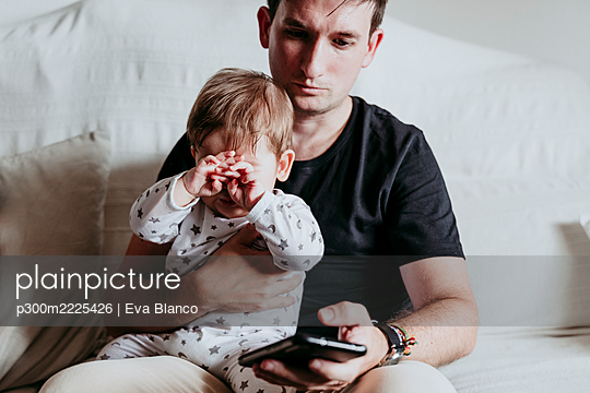 Father using smart phone while sitting with son on sofa at home - p300m2225426 by Eva Blanco
