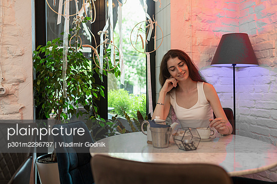 Young woman enjoying tea at cafe table - p301m2296797 by Vladimir Godnik