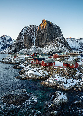 Tranquil snow covered waterfront fishing village and cliffs, Hamnoy, Lofoten Islands, Norway - p1023m2067769 by Anna Wiewiora