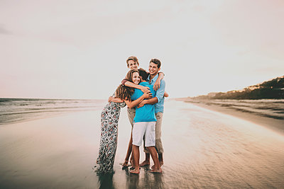 Happy siblings embracing while standing at beach against sky during sunset - p1166m2011181 by Cavan Images