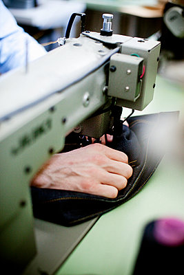 Cropped image of man sewing blue jeans in textile industry - p1185m994537f by Astrakan