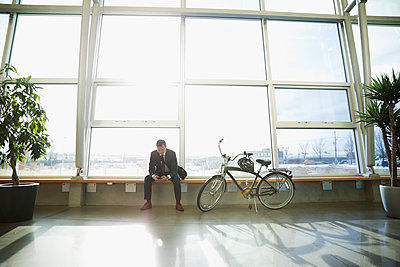 Businessman commuter texting with smart phone next to bicycle in sunny office lobby - p1192m1517069 by Hero Images