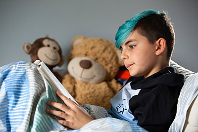 Boy in bed reading book - p1211m2168828 by Danny Weiss