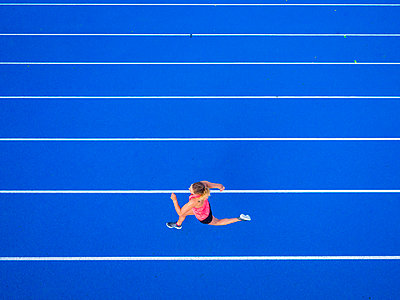 Top view of female runner on tartan track - p300m2069435 by Stefan Schurr