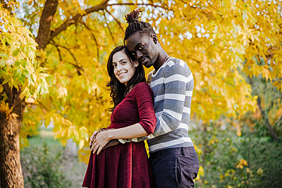 Smiling multi ethnic couple with hands on stomach standing in park during autumn - p300m2240370 by Eva Blanco