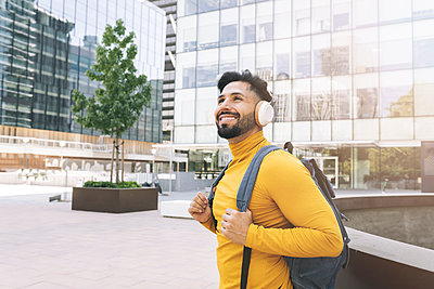 Smiling man with headphones and backpack in city - p300m2300111 von Jose Carlos Ichiro