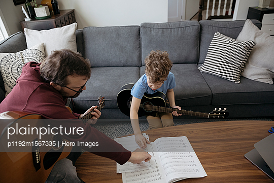 Father teaching son how to play guitar, reading sheet music in living room - p1192m1567335 by Hero Images
