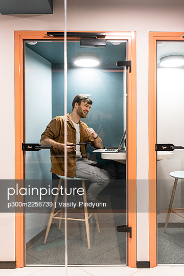 Male professional talking on video call through laptop seen through glass door in office - p300m2256739 by Vasily Pindyurin