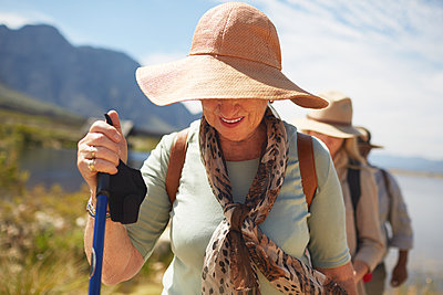 Active senior woman in sun hat hiking - p1023m1561148 by Trevor Adeline