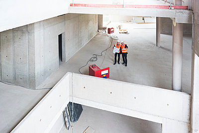 Two men with plan wearing safety vests talking in building under construction - p300m1459733 by Daniel Ingold