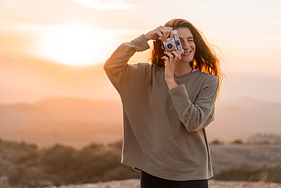 Spain, Barcelona, Natural Park of Sant Llorenc, woman taking a picture with vintage camera at sunset - p300m2058573 von VITTA GALLERY