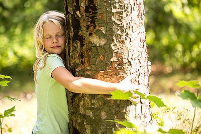 Little girl hugging tree in forest - p300m2160749 von Fotoagentur WESTEND61