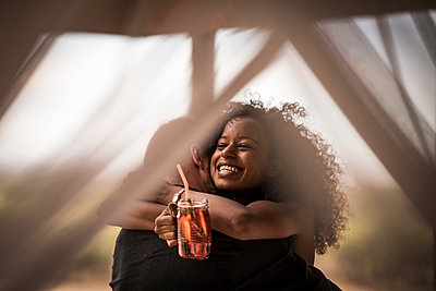 Happy woman holding fresh ice tea drink hugging man - p300m2170629 by Malte Jäger