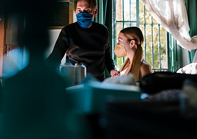 Male hairstylist and customer wearing protective face mask at salon - p300m2274247 by Ezequiel Giménez