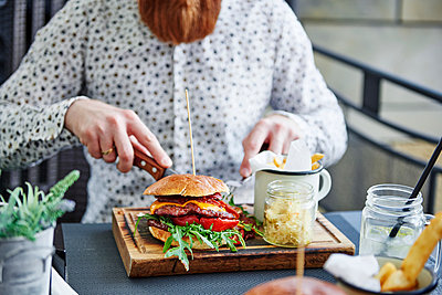 Bearded man eating burger, cropped - p429m2004416 by Gpointstudio