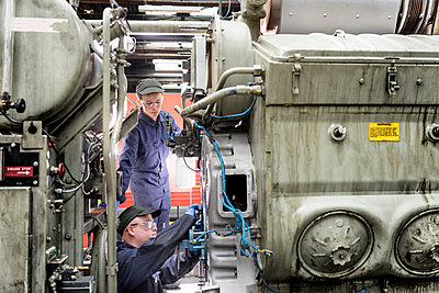 Apprentice watching engineer working on locomotive engine in train works - p924m1480616 by Monty Rakusen