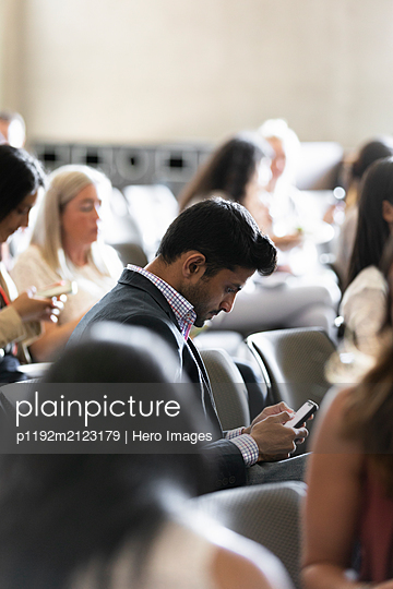 Businessman using smart phone in conference audience - p1192m2123179 by Hero Images