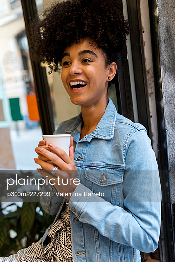Smiling woman drinking coffee while sitting by window at cafe - p300m2227299 by Valentina Barreto