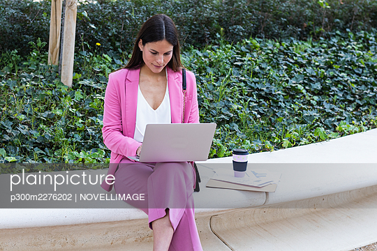 Young female entrepreneur using laptop while working on retaining wall - p300m2276202 by NOVELLIMAGE