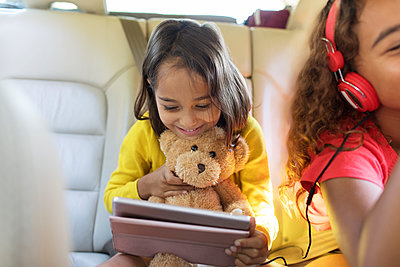 Cute girl with teddy bear using digital tablet in back seat of car - p1023m2066617 by Sam Edwards