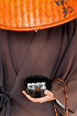 Close up of Japanese monk wearing traditional clothing holding alms bowl. - p1100m1520344 by Mint Images