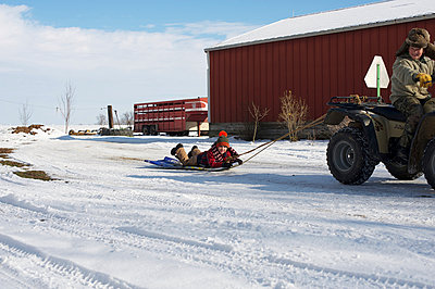 grandpa pulling child on sled with four wheeler  - p1169m1032694 by Tytia Habing