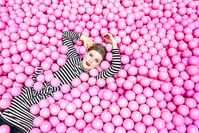 Woman lying in ball pool - p1332m2055022 by Tamboly