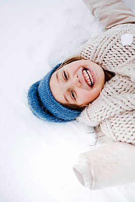 Cheerful girl with scarf lying on snow during winter - p300m2256087 by Katharina Mikhrin